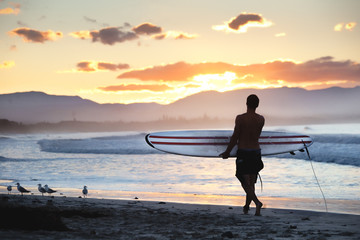 Surfer walking on the shore along the beach lokking at the stunning sunset in Byron Bay, NSW, Australia.
