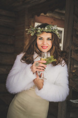 Beautiful bride with glass of champagne outdoors on winter evening