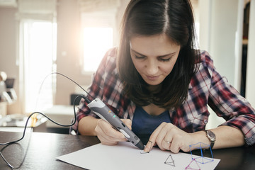 Young woman drawing with 3D pen
