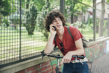 Young man with bicycle on the phone