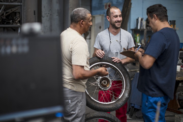 Mechanics standing together in motorcycle workshop