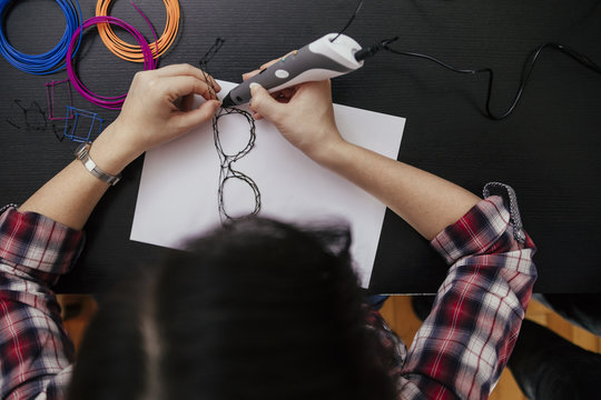 Young woman drawing spectacles with D pen
