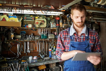 Modern bearded mechanic using tablet in workshop, focus on shelves with equipment and tools  behind him