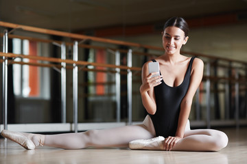 Beautiful smiling ballerina sitting on floor in dance studio elegantly and holding smartphone in hand texting or taking photo