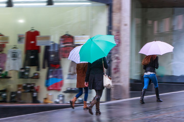 Storm weather. People with umbrellas, pedestrians on the sidewalk in the rain. The storefronts on the city street.