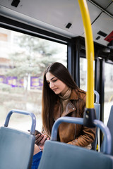 Beautiful young woman sitting in city bus and typing a message on the phone.