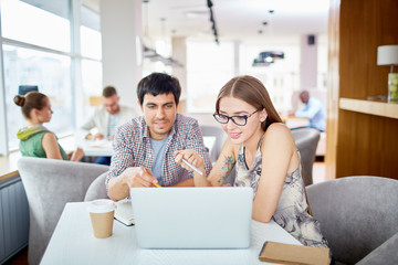 Portrait of two young people, man and woman,  working with laptop at table in modern cafe, pointing at screen and discussing ideas