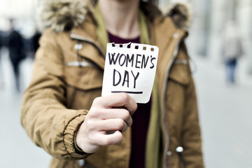woman with a note with the text womens day