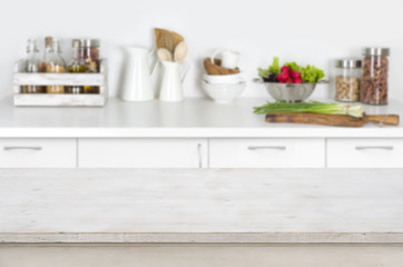 Wooden table on blurred kitchen interior background with fresh vegetables
