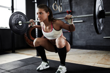 Intense crossfit workout in dark gym: strained young sportswoman performing shoulder press with heavy barbell, standing in start stance
