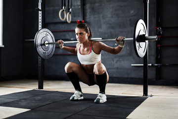 Intense crossfit workout in dark gym: strained young sportswoman ready to perform shoulder press exercise with heavy barbell