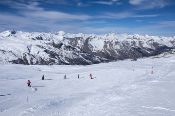 A wide piste, with a group of skiers on the piste, on a clear sunny day in Meribel, in the French Alps