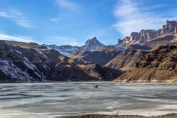 замерзшее озеро в горном ущелье между скал, природа Северного Кавказа