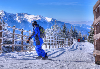 Beautiful winter landscape with a man on ski slope practicing snowboard, on top of mountain in Poiana Brasov, Romania