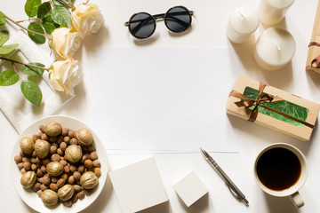 Empty sheet with copy space on the white desk with coffee cup, sunglasses, roses, pen, gifts, candles and vintage white tray. Top view, flat lay, copyspace.