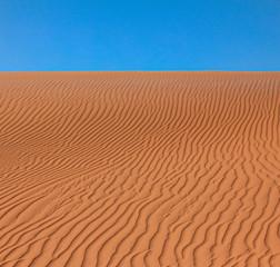 Wavy rippled desert or beach sand texture and blue sky