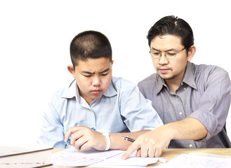 Asian father teaching homework to his 14 years son seriously
