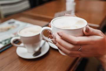 Woman hands holding a cup of coffee with foam over wooden table in cafe