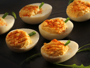 deviled eggs with red pepper on black background