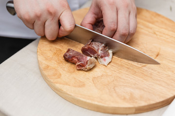 Chef Cutting Raw Meat on The Wood Block.