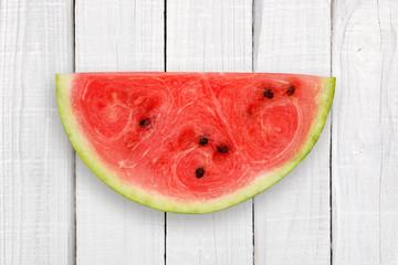 Watermelon slice on white wooden background