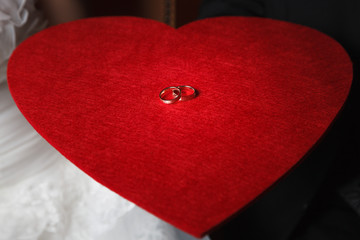 Wedding rings laying on red felt heart