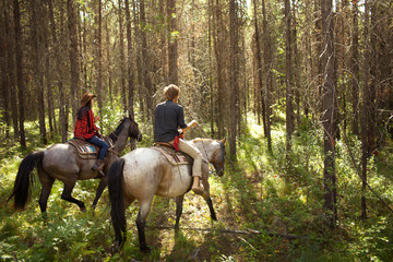 Man and woman riding horses through woods