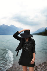 Fashionable woman in hat by lake