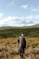 Rear view of man in kilt standing on moor