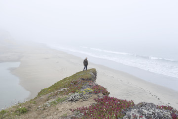 One person standing on rock's edge, high up