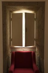 Red chair under shuttered window