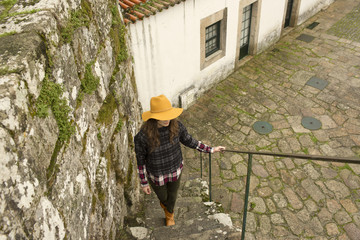 Young woman in yellow hat walking up stone  steps