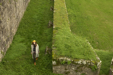 Young woman walking around grassy ramparts