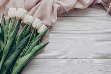 hello spring flat lay. stylish white tulips and beige soft fabric on rustic wooden table background top view. soft light, tenderness atmospheric moment. space for text. rustic wedding