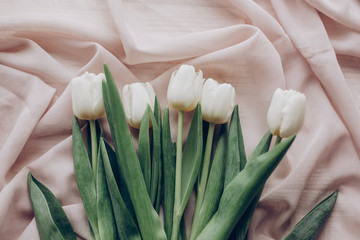 stylish white tulips on beige soft fabric and rustic wooden table background top view. hello spring flat lay. soft light, tenderness atmospheric moment. space for text
