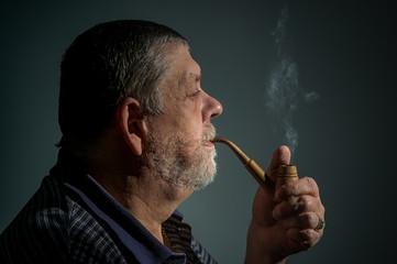 Film toned portrait of Caucasian bearded man smoking tobacco pipe against dark background.