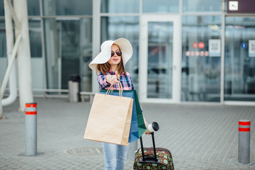 Air travel concept with young hipster businesswoman in big straw hat, sunglasses, plaid shirt with suitcase and disposable cup Freedom Travel and Holiday Concept.