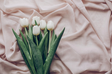 instagram spring flat lay. stylish white tulips on beige soft fabric on rustic table background top view. soft light, tenderness atmospheric moment. space for text. rustic wedding
