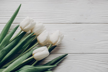 stylish white tulips on rustic wooden table background top view. hello spring flat lay. soft light, tenderness atmospheric moment. space for text. rustic wedding.