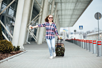 Air travel concept with young hipster businesswoman in plaid shirt with suitcase and disposable cup with coffe or tea. Freedom Travel and Holiday Concept.