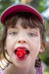 Close up summer portrait of cute young girl in pink cap eating a strawberry.