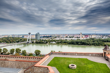 Panoramic view with dramatic sky over Bratislava skyline and river Danube. View from Bratislava castle.