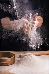 mani femminili che setacciano farina in cucina