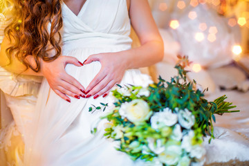 Pregnant girl in white dress, her hands on her stomach in form of heart