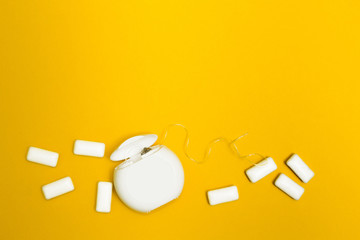 Chewing gum and dental floss on a yellow background. Space for text.