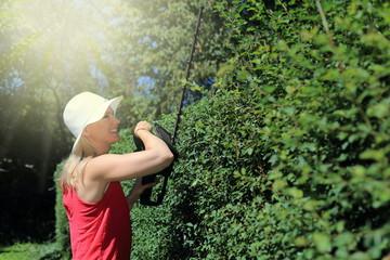 Frau beim Heckenschneiden mit Akku Heckenschere