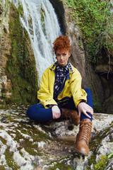 Chica joven y pelirroja posando frente a una cascada en una montaña