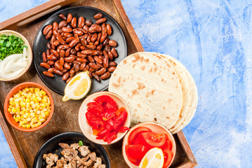 Ingredients for Mexican food on a tray: beans, stew beef, corn, tomatoes, red pepper, onion, herbs, tortillas taco, top view copy space