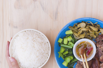 Stewed pork leg set and rice with hand and chopsticks over wooden table