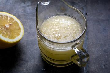 Fresh lemon juice in glass jug, elevated view